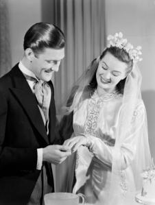 Groom looking at his wifes wedding ring c 1949.