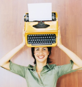 Woman holding typewriter above head, smiling, portrait
